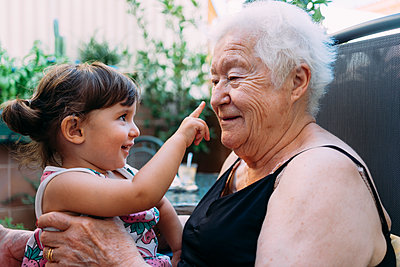 Grandmother and baby girl playing together on the terrace - p300m2029080 by Gemma Ferrando