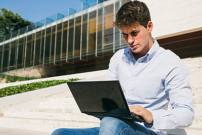Handsome young man using laptop on sunny day - p300m2220453 by Andrés Benitez