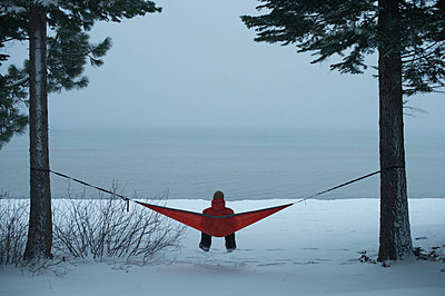 Person Relaxing On Hammock Enjoying A Winter Storm On The South Shore Of Lake Tahoe - p343m1223863 by Brandon Huttenlocher