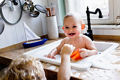 Boy playing with baby brother bathing in kitchen sink - p429m1156104 by Emely