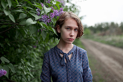 Pensive Caucasian woman standing near flowers - p555m1532797 by Vyacheslav Chistyakov