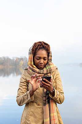 Dark-skinned woman using smartphone on the lakefront - p975m2228203 by Hayden Verry