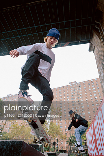 Low angle view of friends skateboarding against buildings in city - p1166m2112552 by Cavan Images
