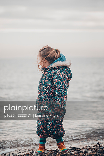 Little girl in winter clothes near the sea - p1628m2222171 by Lorraine Fitch