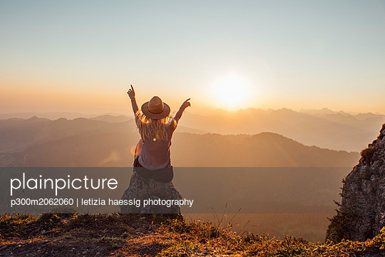 Switzerland, Grosser Mythen, young woman on a hiking trip sitting on a rock at sunrise - p300m2062060 by letizia haessig photography