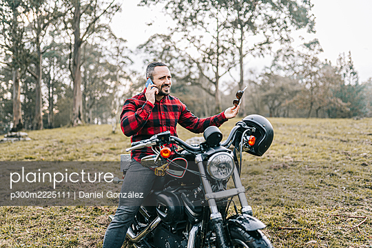 Male biker talking on smart phone while sitting on motorcycle in forest - p300m2225111 by Daniel González