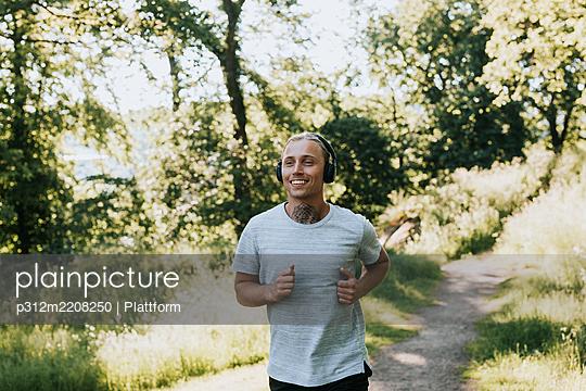 Smiling man jogging - p312m2208250 by Plattform
