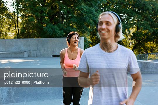 Smiling woman jogging - p312m2216980 by Plattform