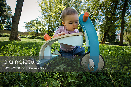 Portrait of baby girl playing with tricycle on a lawn in a park. - p429m2190406 by Stefano Oppo