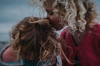 Girl kissing sister at beach - p1166m1489628 by Cavan Images