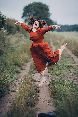 Braunhaarige Frau im roten Kleid tanzt auf einem Feldweg - p1628m2288927 von Lorraine Fitch