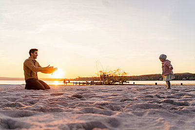 Germany, Bavaria, Herrsching, father and daughter playing on the beach at sunset - p300m2102715 von Daniel Ingold