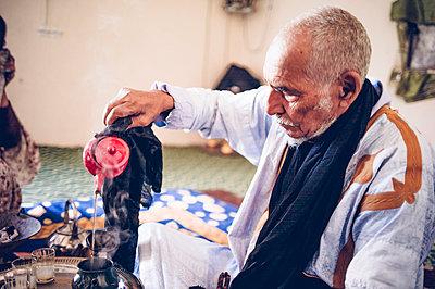 Senior man in Smara refugee camp preparing tea, Tindouf, Algeria - p300m2160652 von Oscar Carrascosa Martinez