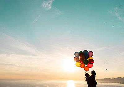 Man carrying daughter holding colorful balloons during sunset - p300m2275670 by DREAMSTOCK1982