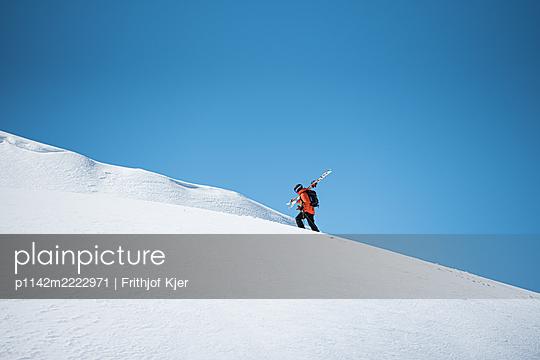 Skifahrer beim Aufstieg mit Skiern über der Schulter - p1142m2222971 von Frithjof Kjer