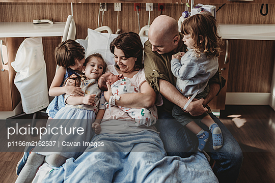 Mid view of whole family holding newborn son in hospital - p1166m2162537 by Cavan Images