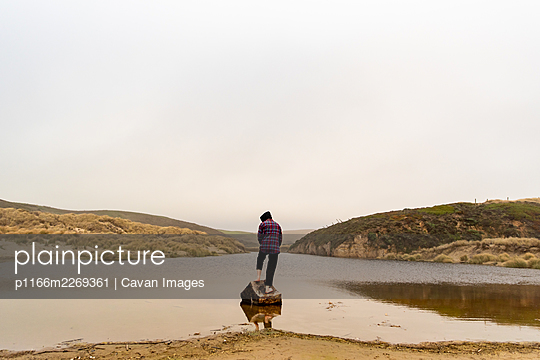One person standing on log at edge of coastal water in front of hillsO - p1166m2269361 by Cavan Images