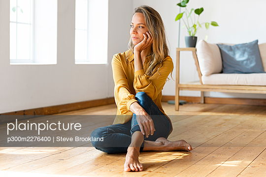 Thoughtful woman looking away while sitting with hand on chin on floor at home - p300m2276400 by Steve Brookland