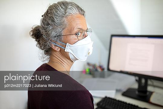 Woman wearing face mask in office - p312m2217023 by Juliana Wiklund