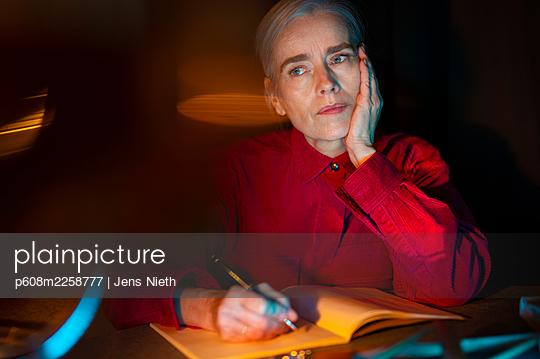 Elderly woman writing a diary - p608m2258777 by Jens Nieth