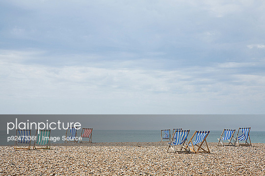 Deckchairs on beach - p9247336f by Image Source