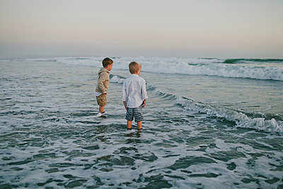 Carefree brothers standing in sea against clear sky during sunset - p1166m1530877 by Cavan Images