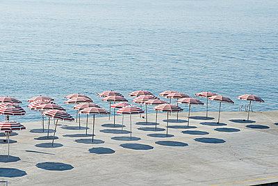 Sun umbrellas on concrete promenade - p1292m1122901 by Niels Schubert