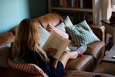 Pretty woman reading a book on sofa at home - p1315m1186400 by Wavebreak