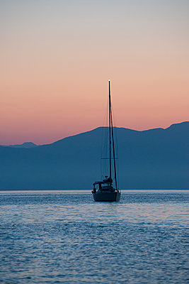 A sailing yacht at anchor in the early morning light before a range of mountains along the coast. - p1433m1529110 by Wolf Kettler