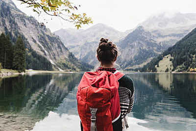 Austria, Tyrol, Alps, hiker standing at mountain lake - p300m1505747 by Uwe Umstätter