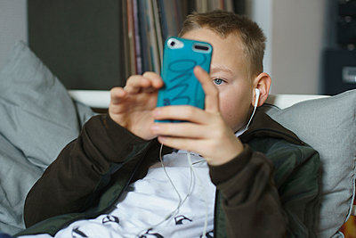 Boy listening music while using smart phone at home - p301m1482430 by Halfdark