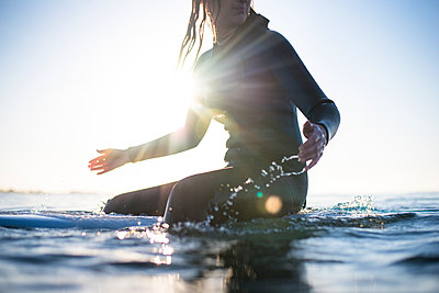 Woman sitting on surfboard in sea - p343m2026017 by Cate Brown