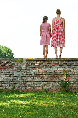 Two girls standing on brick wall - p763m1355504 by co-o-peration
