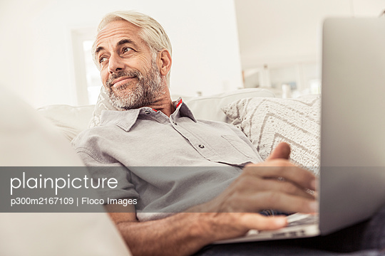 Mature man using laptop on couch at home - p300m2167109 by Floco Images