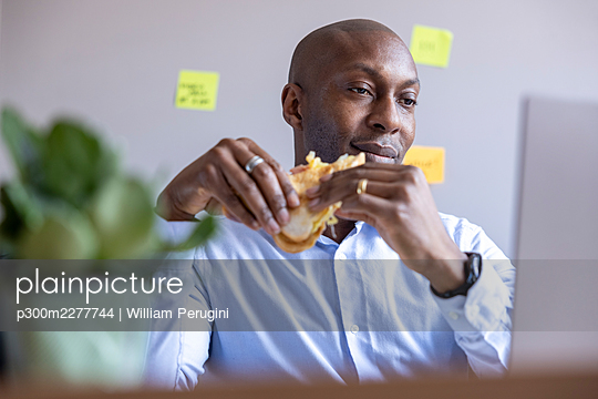 Businessman holding sandwich while looking at laptop in office - p300m2277744 by William Perugini