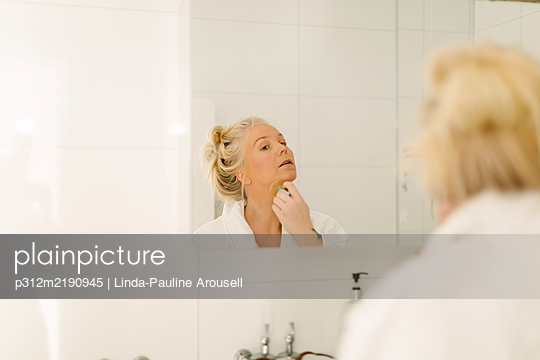 Woman doing make-up in bathroom - p312m2190945 by Linda-Pauline Arousell