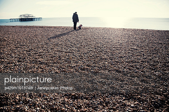 Silhouetted view of Brighton pier and man with toddler daughter on beach, Brighton, Sussex, UK - p429m1013748f by Janeycakes Photos
