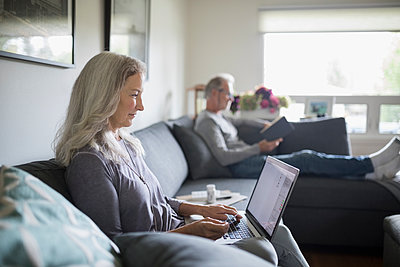 Senior woman using laptop on living room sofa - p1192m1529643 by Hero Images