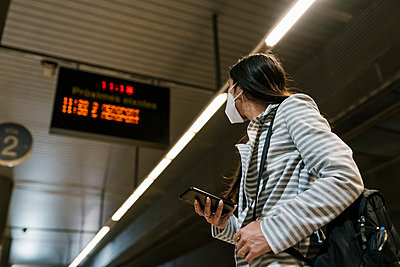 Woman looking away while standing with smart phone waiting at railroad station - p300m2240720 by Ezequiel Giménez