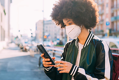 Young woman wearing protective face mask using mobile phone - p300m2286246 by Eugenio Marongiu