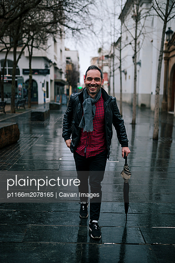 man walks down the street smiling with his umbrella - p1166m2078165 by Cavan Images