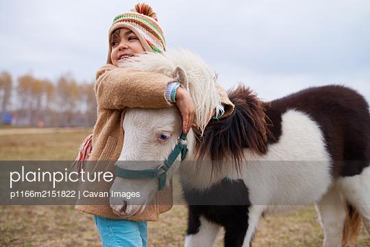 Happy Girl Hugging Little Pony - p1166m2151822 by Cavan Images