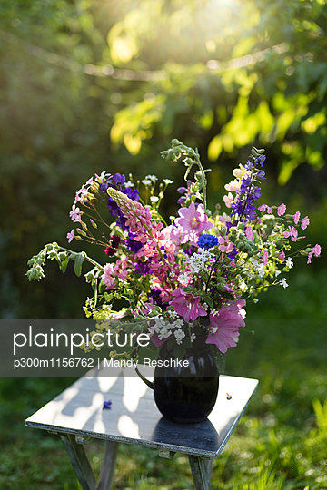 Summer flowers in vase, lupine, hollyhock, cornflower, lady\'s mantle and bellflower