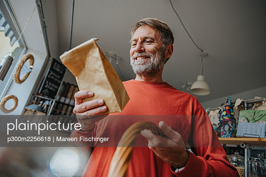 Happy mature man looking at brown package while standing in retail store - p300m2256618 by Mareen Fischinger