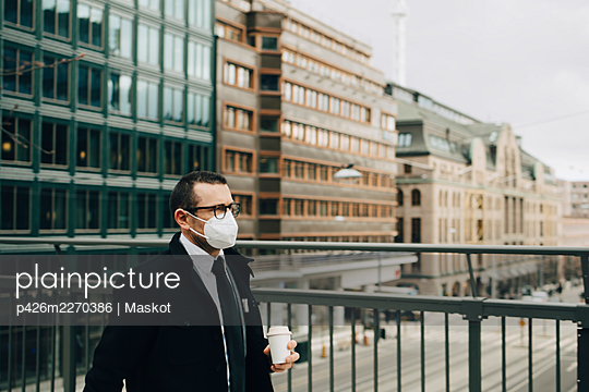 Male entrepreneur with coffee cup by railing in city during pandemic - p426m2270386 by Maskot