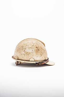 A worn, scratched and dirty white hard hat or safety helmet on a white background - p1302m2126957 by Richard Nixon