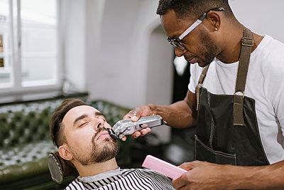Barber cutting beard of a customer in barber shop - p300m2113951 von Hernandez and Sorokina
