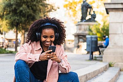 Happy afro young woman using mobile phone while listening music on staircase in city - p300m2243962 by NOVELLIMAGE