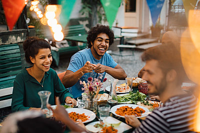 Cheerful male and female friends enjoying during dinner party in backyard - p426m2046205 by Maskot