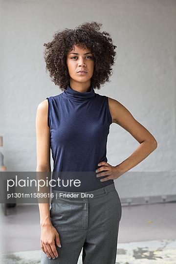 Attraktive Geschäftsfrau mit Afro steht ausdrucksstark in einem modernen Büro - p1301m1589616 von Delia Baum